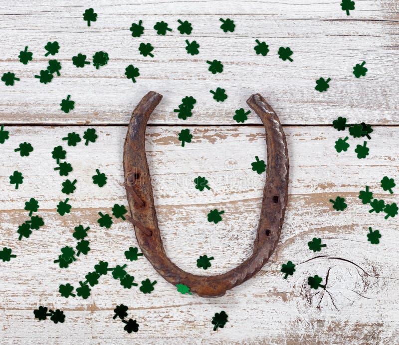 Ржавая подкова с shinny клевера на день St. Patrick стоковые фото