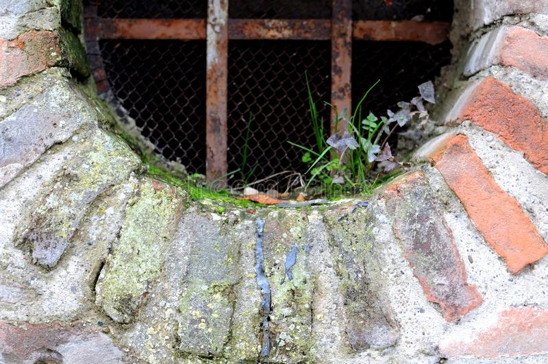 Ржавая решетка на отверстии в стене города стоковые изображения