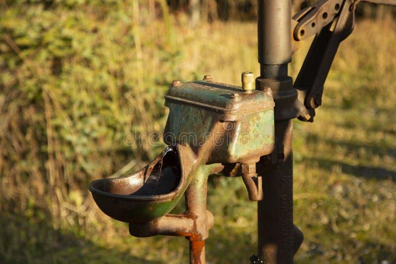 Ржавая старая водяная помпа колодезной воды которая все еще активна стоковые изображения