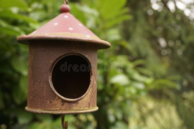 Ржавая старая смертная казнь через повешение дома птицы в саде стоковая фотография