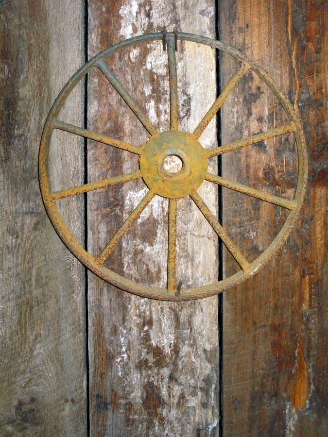 Ржавое античное колесо телеги пригвозженное к двери амбара стоковые изображения
