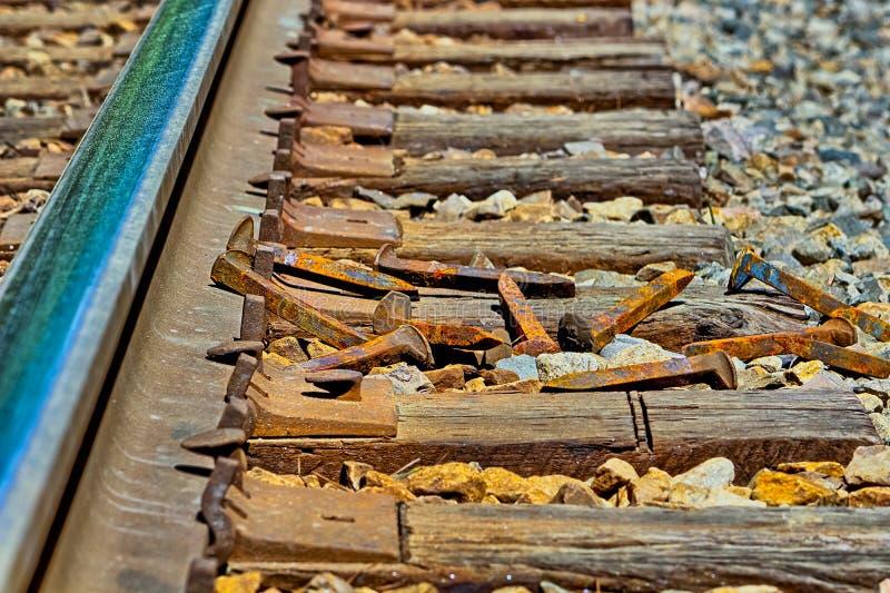 Ржавые железнодорожные шипы кладя на землю в куче стоковые фотографии rf