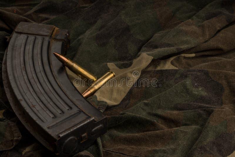 Ржавые кассета и пули AK-47 на предпосылке ткани камуфлирования стоковая фотография rf
