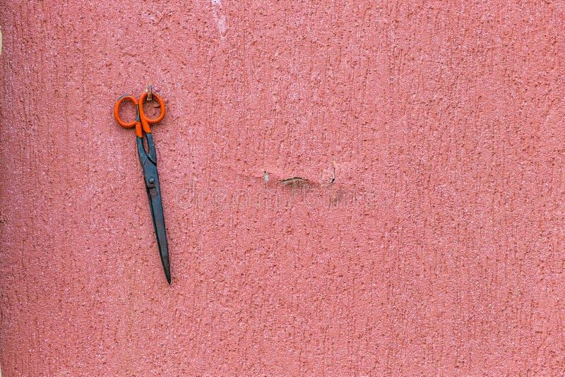 Ржавые ножницы на старой стене стоковые фото