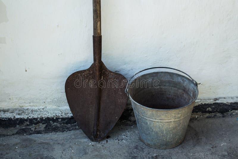 Ржавые лопаткоулавливатель и ведро на белой предпосылке стоковое фото rf