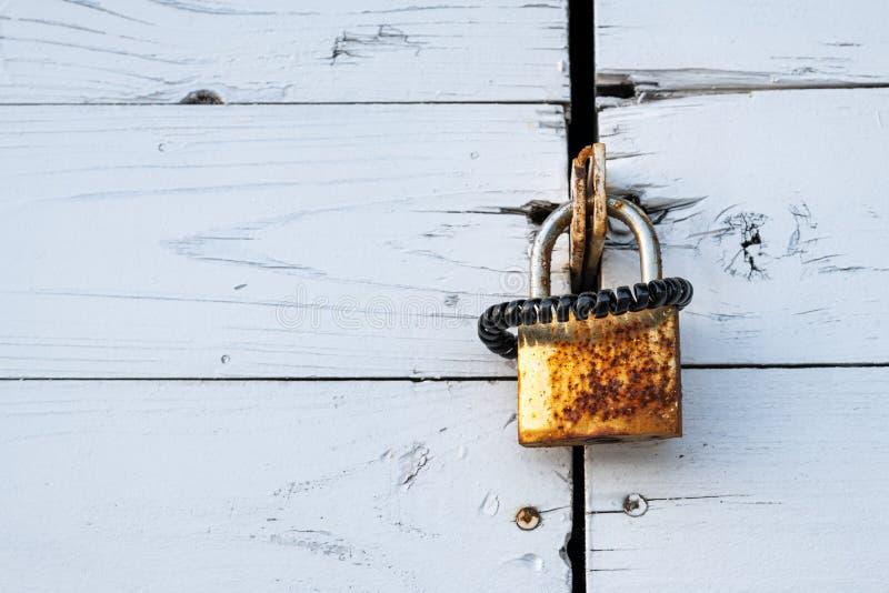 Ржавый замок с черной scrunchy смертной казнью через повешение на деревянной двери стоковое фото rf