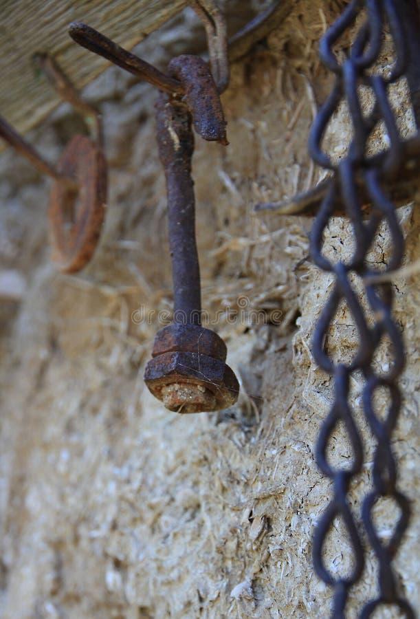 Ржавый изогнутый болт с гайкой на старом крюке вешалки стоковое изображение