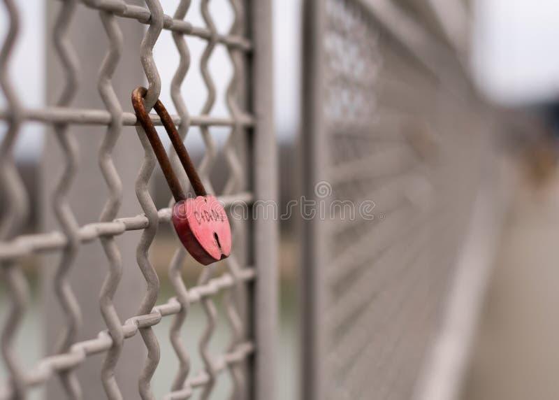 Ржавый красный padlock влюбленности запертый к мосту стоковые фото