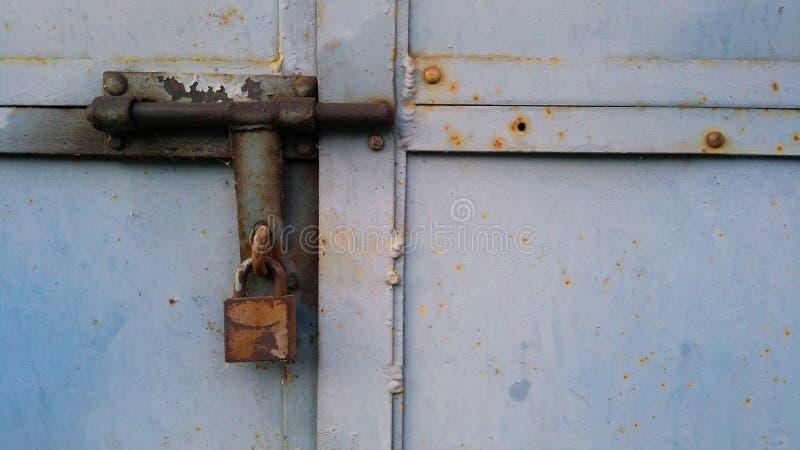 Ржавый старый замок вися на ржавой выдержанной двери утюга, который заперли вверх стоковые изображения