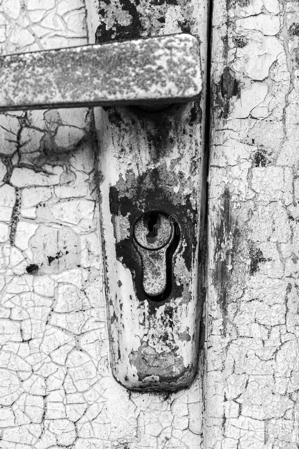 Ржавый старый замок с затрапезной ручкой металла на фоне двери с треснутой краской стоковое фото rf