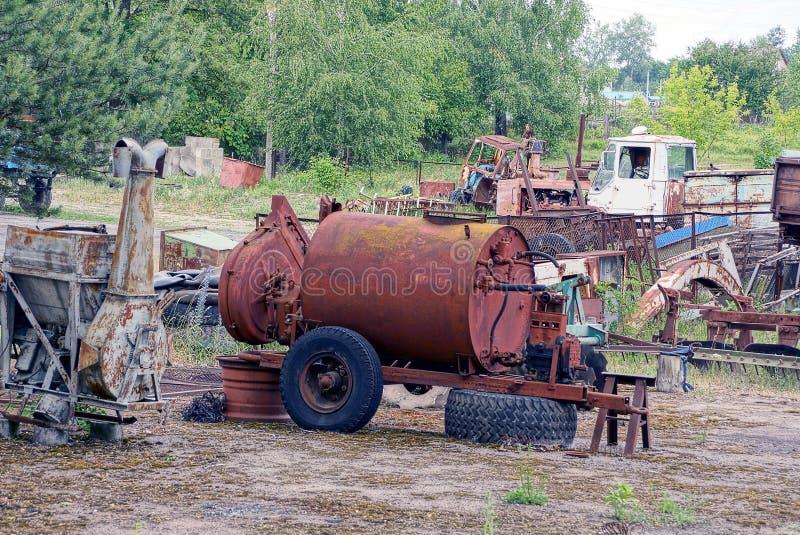 Ржавый танк на колесах среди старых оборудования и металлолома стоковая фотография rf