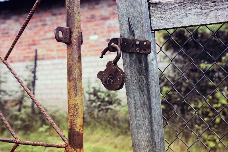 Ржавый padlock открытый на старых воротах стоковая фотография