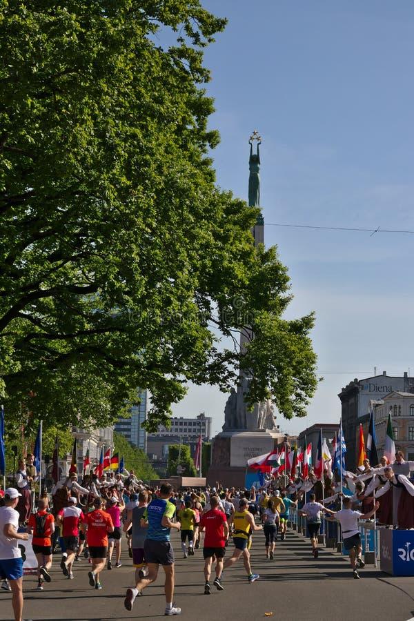 Рига, Латвия - 19-ое мая 2019: Марафонцы достигая статую свободы с традиционно одетыми чирлидерами дают высокие fives стоковые фото