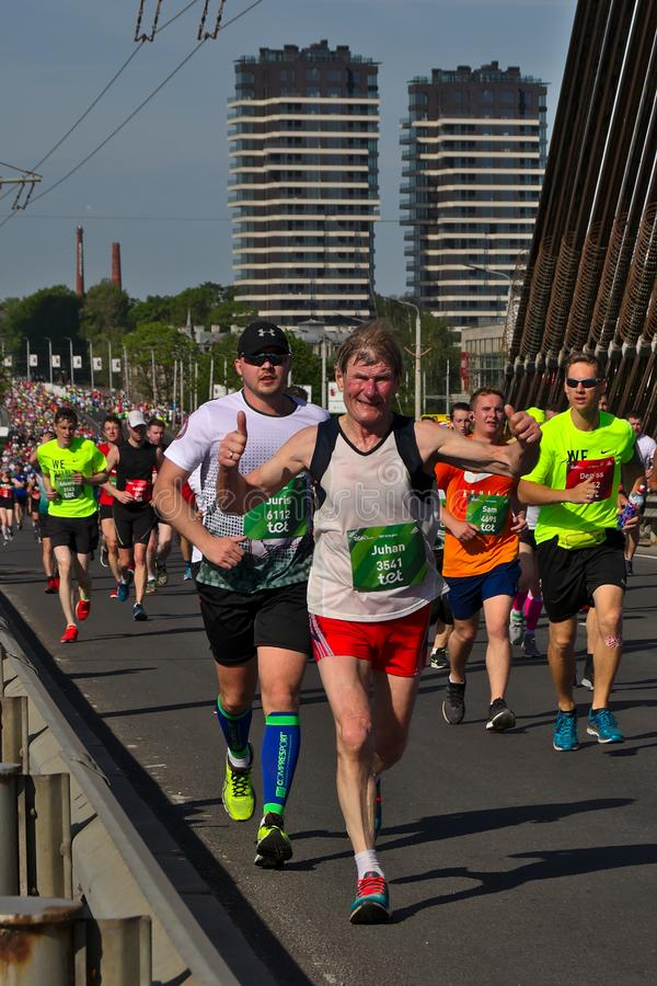 Рига, Латвия - 19-ое мая 2019: Пожилой марафонец храбро пересекая мост стоковое изображение rf