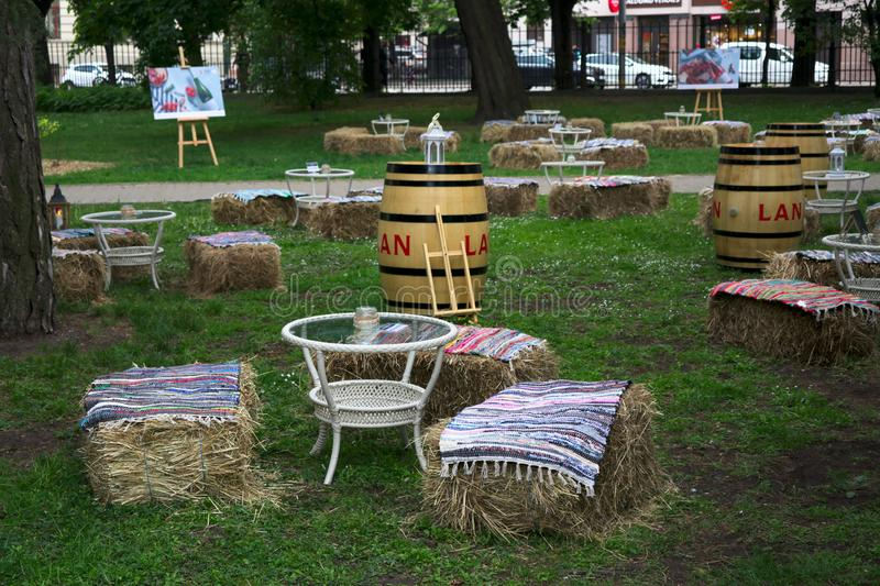 Рига, Латвия - 24-ое мая 2019: Уютная смотря терраса для того чтобы насладиться напитками в парке стоковая фотография rf