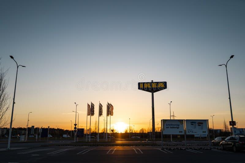 РИГА, ЛАТВИЯ - 3-ЬЕ АПРЕЛЯ 2019: Знак бренда IKEA во время темного вечера и ветра - голубого неба на заднем плане стоковое фото rf