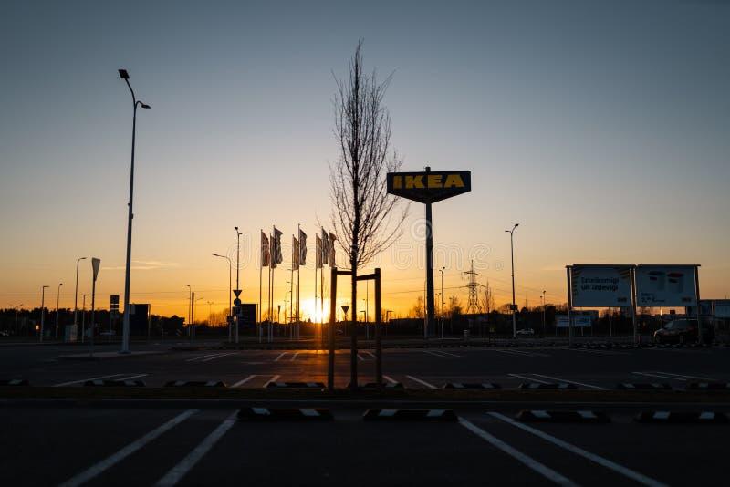 РИГА, ЛАТВИЯ - 3-ЬЕ АПРЕЛЯ 2019: Знак бренда IKEA во время темного вечера и ветра - голубого неба на заднем плане стоковые изображения