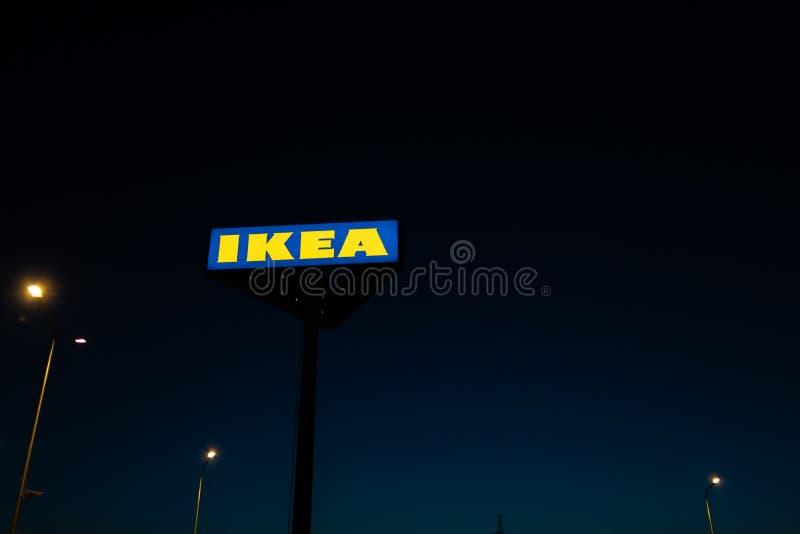 РИГА, ЛАТВИЯ - 3-ЬЕ АПРЕЛЯ 2019: Знак бренда IKEA во время темного вечера и ветра - голубого неба на заднем плане стоковое фото