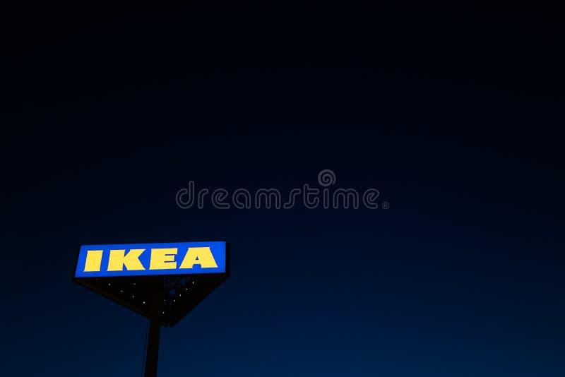 РИГА, ЛАТВИЯ - 3-ЬЕ АПРЕЛЯ 2019: Знак бренда IKEA во время темного вечера и ветра - голубого неба на заднем плане стоковое изображение rf