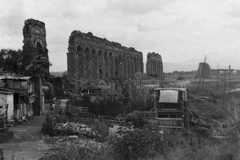 РИМ, ИТАЛИЯ, 1966 - руины римского акведука домашние к некоторым плохим казармам стоковые изображения rf