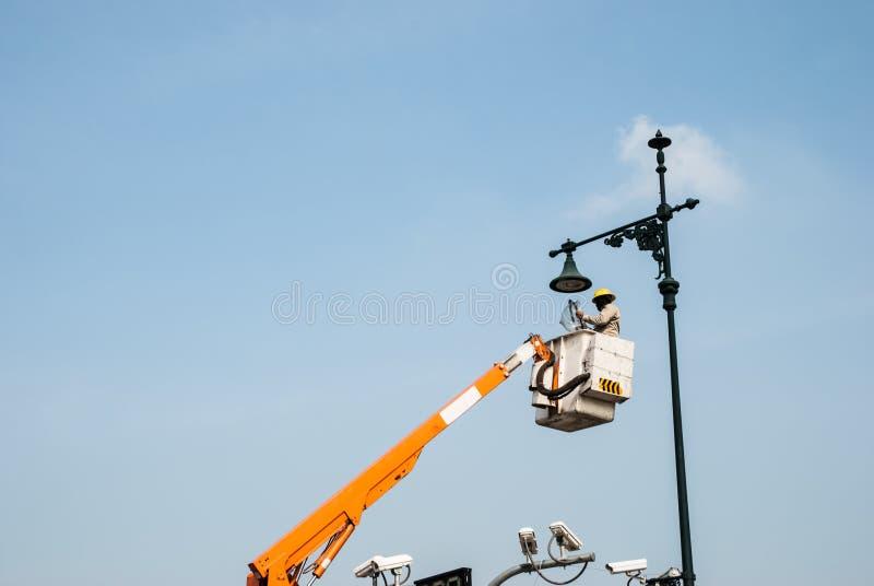 Рискованая работа, высокий уборщик lambpost стоковые фото