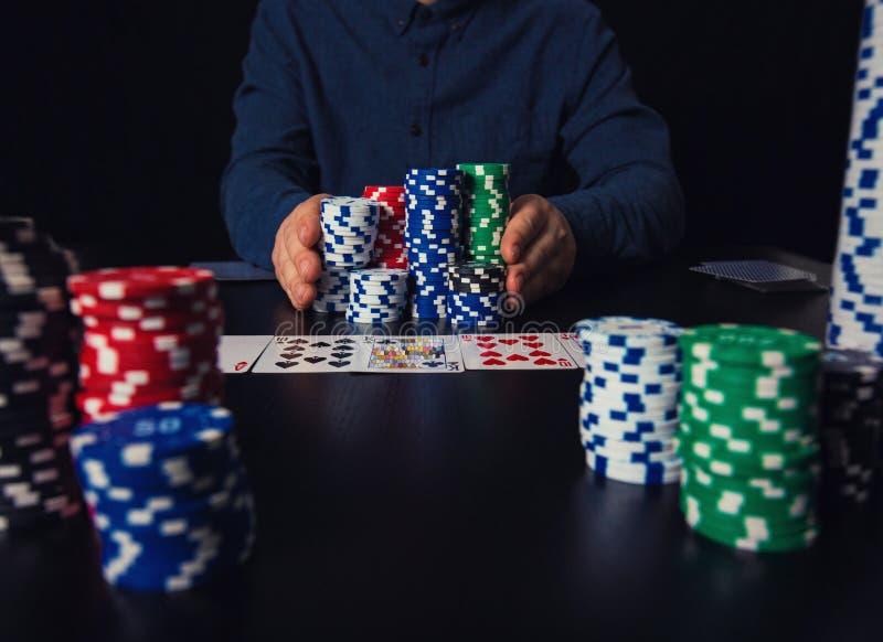 Рискованый игрок в покер парня идя все-в нажимать его большой стог обломоков вперед, держа пари на таблице игры казино gambling стоковое изображение rf