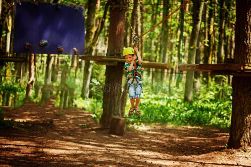 Рискуйте взбираясь парк натянутой проволоки - маленький ребенок на курсе в шлеме и оборудовании для обеспечения безопасности горы стоковое фото