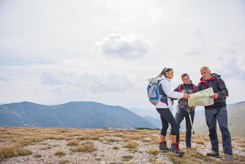 Рискуйте, путешествуйте, туризм, поход и концепция людей - группа в составе усмехаясь друзья с рюкзаками и картой outdoors стоковое изображение rf