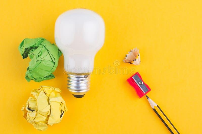 Рисуйте, скомкайте бумагу и шарик над желтой предпосылкой стоковое фото