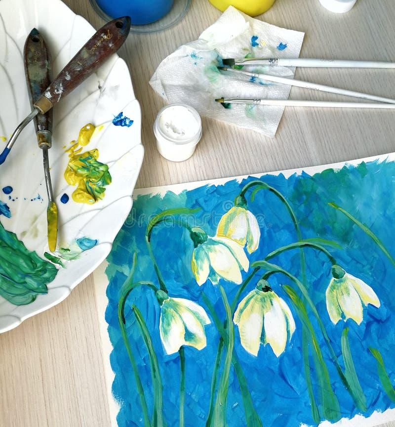 Рисующ с цветками, нарисованными профессиональными художественными материалами акварели и гуаши, холст конца-вверх, палитра и стоковое изображение