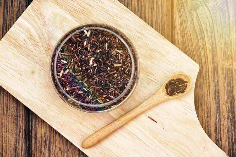 Рис зерен ягоды риса фиолетовый на деревянной плите, ест чистую концепцию стоковые фотографии rf