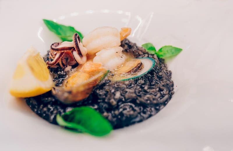 Рис черноты спагетти с морепродуктами в sause с куском лимона спагетти с чернилами кальмара раковин scallops с креветками, мидиям стоковое фото