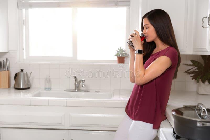Ритуалы утра, чай чашки кофе женщины выпивая в кухне рядом с окном с солнечным светом стоковая фотография rf