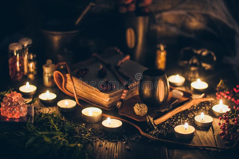 Ритуальная сцена со свечами, сеть паука колдовства хеллоуина, винтажные бутылки на деревенской предпосылке со страшным черепом f стоковое фото rf