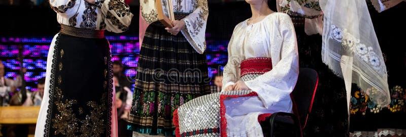 Ритуал свадьбы в румынских традиционных folkloric костюмах и танцорах стоковое фото rf
