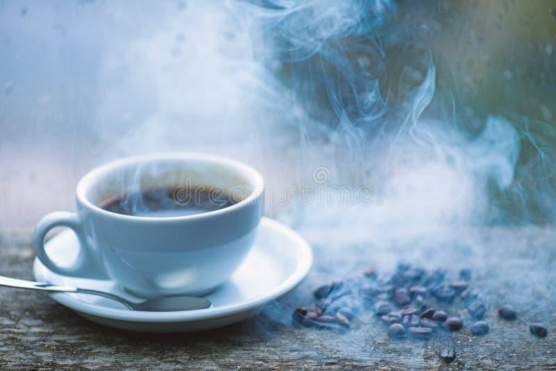 Ритуал утра кофе Свежие заваренные кружка и фасоли кофе белые на windowsill Влажные стеклянное окно и чашка горячего кофе стоковое изображение rf