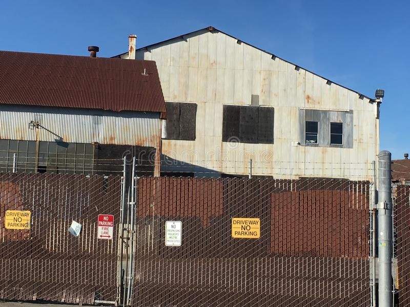 Рифлёные промышленные здания безопасно за ограждать покрытый с колючей проволокой стоковые фотографии rf