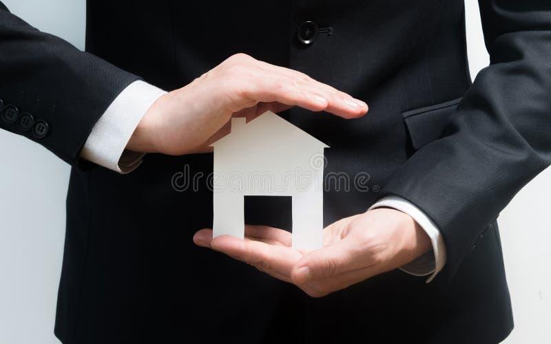 Риэлтор, агент недвижимости держа модель бумаги дома Получать, что доступ самонавести Вклад и покупая концепция свойства стоковые фото