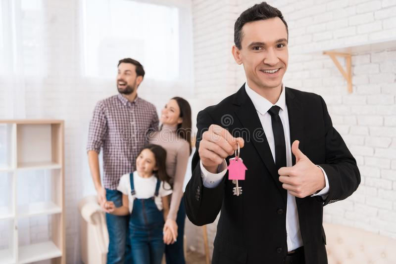 Риэлтор в костюме держит ключи с ключом обманывает в форме дома Молодая семья смотрит квартиру стоковые изображения