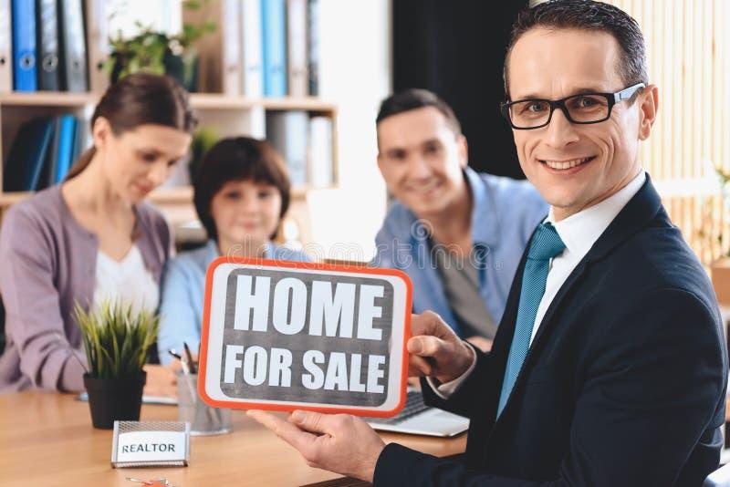 Риэлтор сидя на столе в офисе Риэлтор домой для продажи знак с семьей в предпосылке стоковые фото