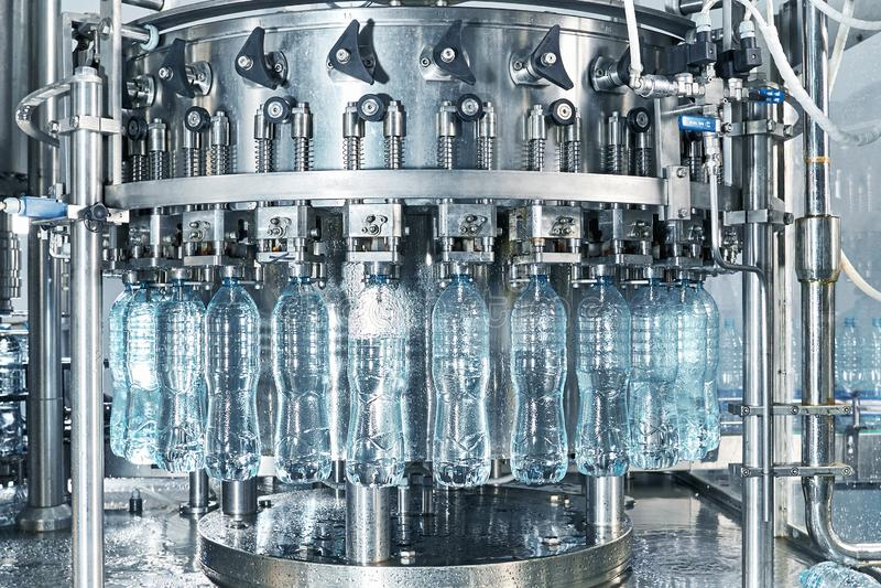 Робототехническая линия фабрики для обработки и разливать по бутылкам чистой ключевой воды стоковое изображение