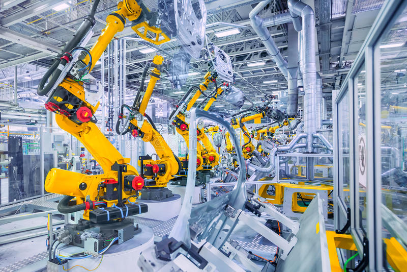 Роботы в заводе автомобиля стоковое изображение
