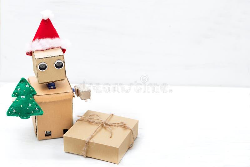 Робот в шляпе santa держит рождественскую елку и подарочную коробку экземпляр стоковая фотография