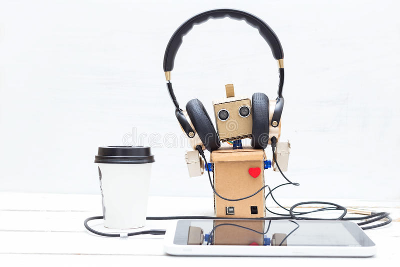 Робот с музыкой красного сердца слушая на таблетке стоковое фото