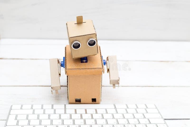 Робот с руками стоящ и работающ за клавиатурой стоковые изображения