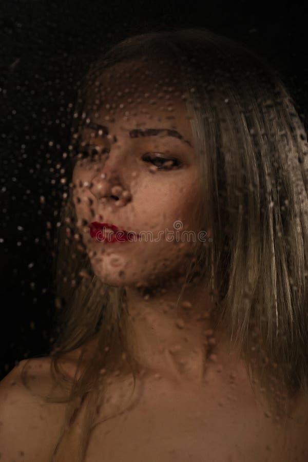 Ровный портрет сексуальной модели, представляя за прозрачным стеклом покрытым водой падает стоковая фотография