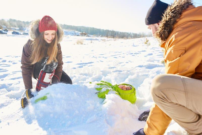 Родители играя с сыном в снеге стоковое изображение