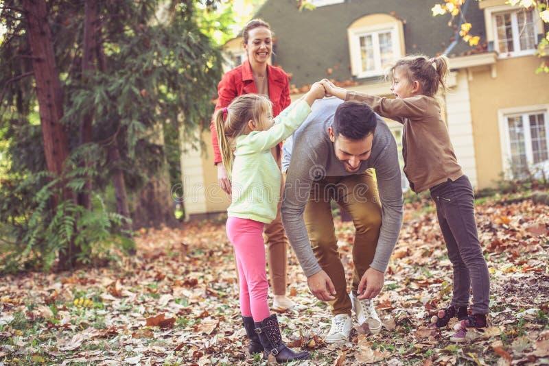 Родители имеют игру с детьми Отец идя под руку стоковая фотография