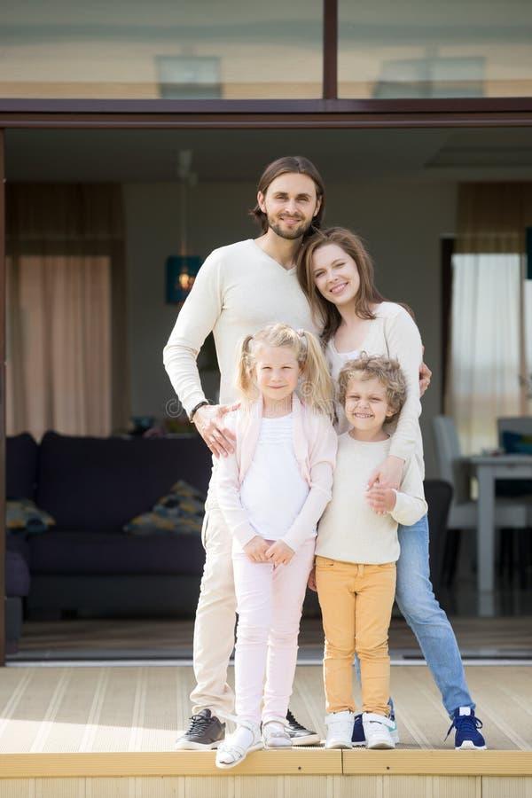 Родители и дети смотря камеру стоя на террасе дома стоковое фото rf