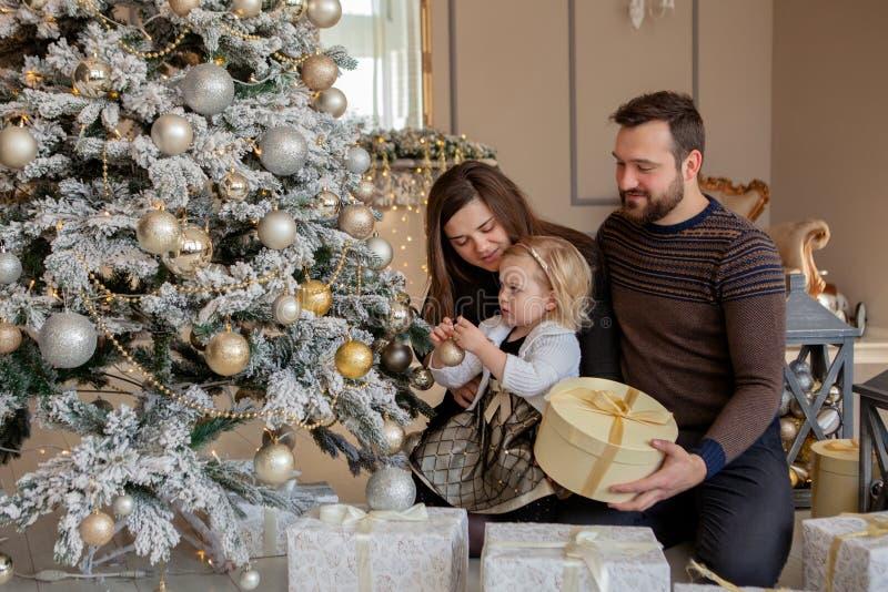 Родители и его маленькая дочь украшая рождественскую елку с игрушками и гирляндами стоковые фотографии rf